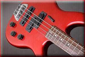 Red bass guitar on a grey backgroung