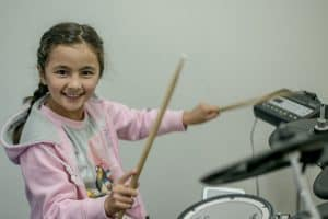Student playing drums at her weekly Sutherland Shire drum lessons at Do Re Mi Studios