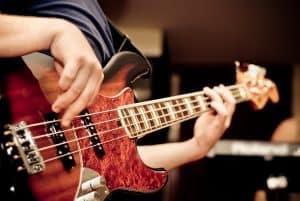 Bass guitarist playing a red bass